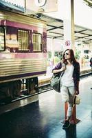 ung hipsterkvinna som väntar på stationsplattformen med ryggsäck foto