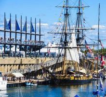 en antik segelbåt och grupper av människor vid den gamla hamnen i Montreal, Quebec, Kanada foto