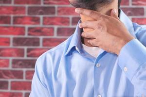 man som håller halsen i smärta
