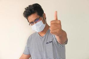 en ung man med skyddande mask visar tummen upp