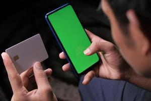 mans hand som håller kreditkort och använder smart telefon för att handla online foto
