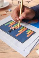 mans hand som skriver på ett stapeldiagram