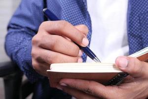 man skriver i ett anteckningsblock
