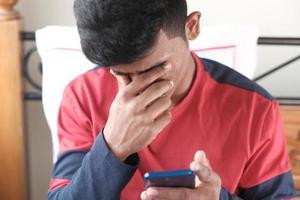 upprörd man tittar på smart telefon