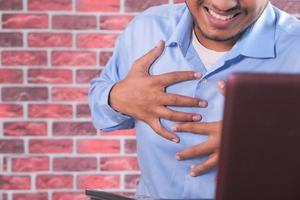 man klämmer fast bröstet i smärta