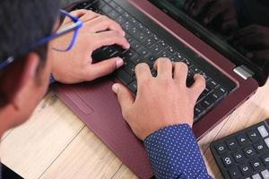 mans handskrivning på bärbar dator foto