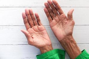 äldre persons händer som isoleras på det vita bordet