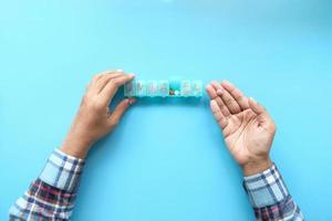 ovanifrån av mans händer som tar medicin från en pillerbox foto