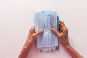 senior kvinnas hand som håller ansiktsmasker