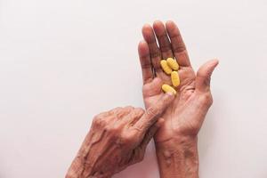 äldre kvinnas hand tar medicin foto