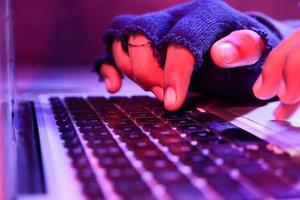 närbild av hackerhand som stjäl data från bärbar dator foto