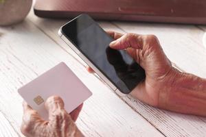 seniors händer som håller en mobiltelefon foto