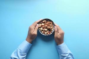 skål med blandade nötter på blå bakgrund