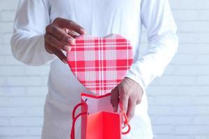 ung man lägger en hjärtformad gåva i en presentpåse