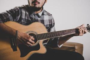 närbild av hipster skägg man hand spelar gitarr foto