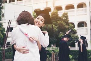 ung kvinnlig examen som kramar sin mamma vid examenceremonin foto