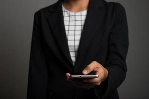ung affärskvinna som använder mobiltelefonen som isoleras på svart bakgrund foto