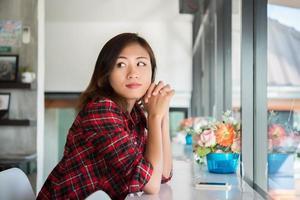 vacker asiatisk kvinna som sitter på ett kafé foto