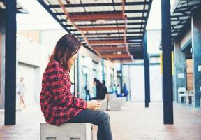 vacker ung hipster sms på sin smartphone sitter på en bänk foto