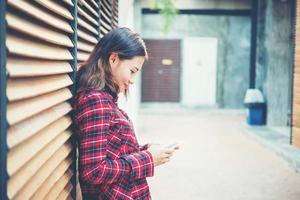vacker ung hipster sms på smarttelefonen foto