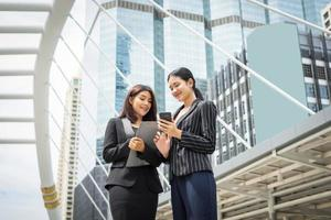 två affärskvinna som använder en smartphone och diskuterar arbete framför kontoret foto
