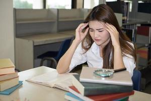 porträtt av student röra huvudet medan du läser bok i college bibliotek foto