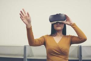 porträtt av ung asiatisk kvinna som bär virtual reality-skyddsglasögon foto