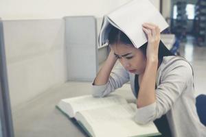 porträtt av en student som täcker hennes huvud med bok foto