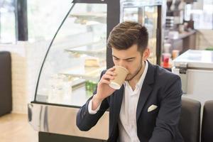 ung affärsman som dricker kaffe