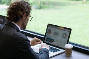ung affärsman som arbetar på bärbara datorn på kontoret foto