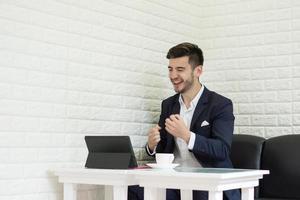 framgångsrik ung affärsman som arbetar på bärbara datorn på kontoret foto