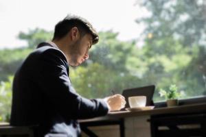 ung affärsman som bär en kostym och använder bärbar dator på ett kafé foto