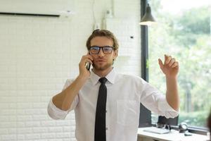 ung affärsman som talar i telefon medan han arbetar på kontoret foto