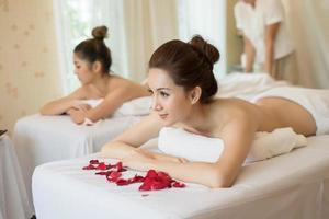vackra leende kvinnor med blommor som vilar i spaet före massage foto