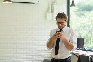 ung affärsman som använder smartphonen medan han arbetar på kontoret foto