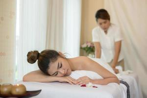 ung vacker kvinna med hälsosam massage i en spasalong foto