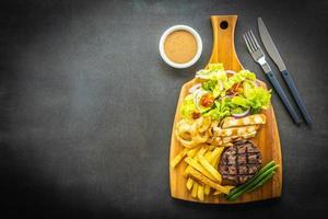 grillad biff med pommes frites, sås och färska grönsaker foto