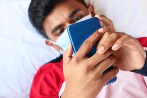 man i kirurgisk ansiktsmask med smart telefon