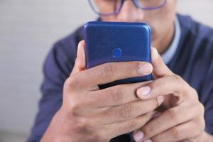 närbild av ung mans hand med smart telefon foto