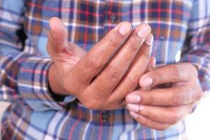 man som lider av smärta i handen på nära håll