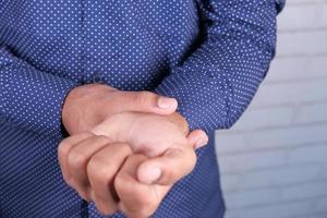 man lider smärta i handen på nära håll