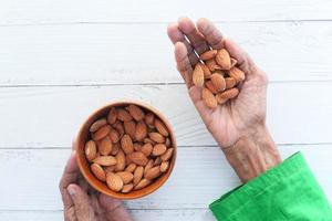 äldre kvinnas hand som håller en skål på mandlar