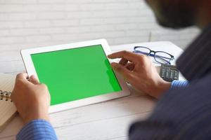 affärsman som använder digital tabletmodell på ett kontorsskrivbord foto