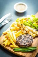 grillad biff med pommes frites, sås och färska grönsaker