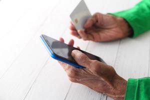äldre kvinna handlar online foto
