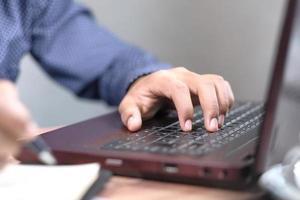närbild av manhand att skriva på bärbar dator foto