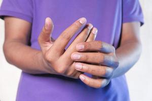 man håller fingret i smärta