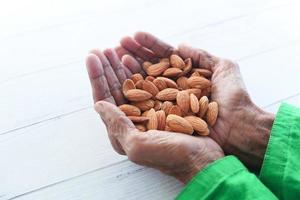 äldre kvinnas hand som håller mandlar