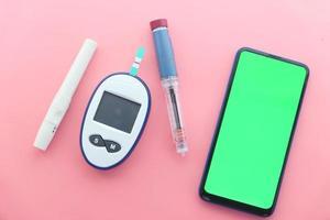 insulin och smart telefon på rosa bakgrund foto