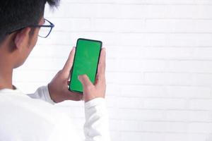 bakifrån av ung man använder smart telefon inomhus foto